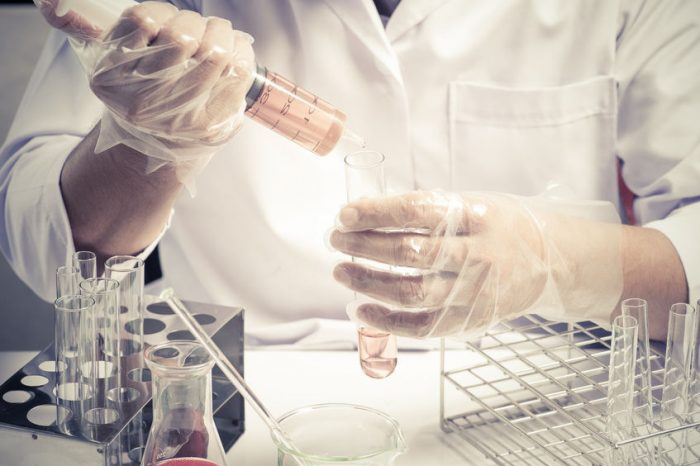 45135467 - conical flask in scientist hand with lab glassware background, laboratory research concept