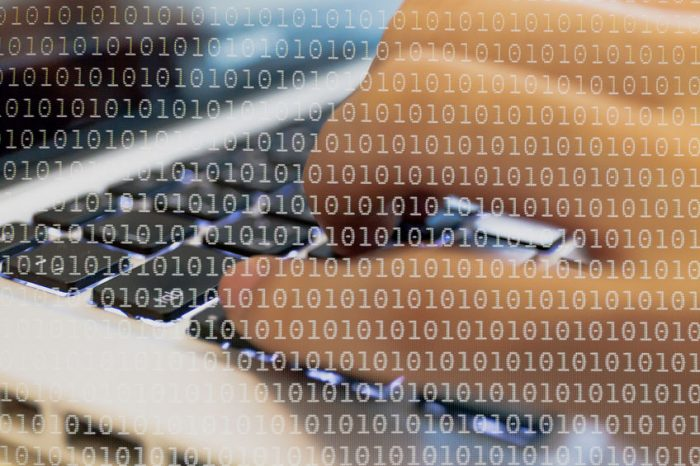 49135288 - double exposure of a programmer coding on his laptop dissolved with binary code background